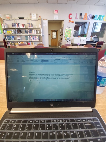 authors black laptop computer on wooden tabletop in a school library with short story on screen